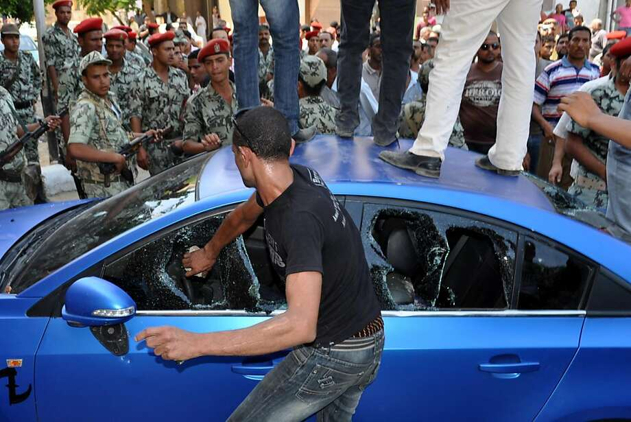 An Egyptian demonstrator breaks the windows of a car in the Egyptian canal city of Suez on July 6, 2011 as hundreds of people torched police cars and tried to storm government buildings, after a court confirmed the bail of police accused of murdering protesters. Photo: -, AFP/Getty Images