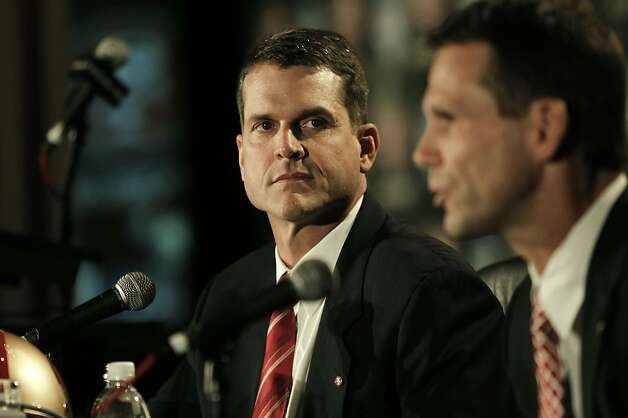 The 49ers' new head coach, Jim Harbaugh, listens to general manager Trent Baalke at a news conference in San Francisco on Friday. Photo: Michael Macor, The Chronicle