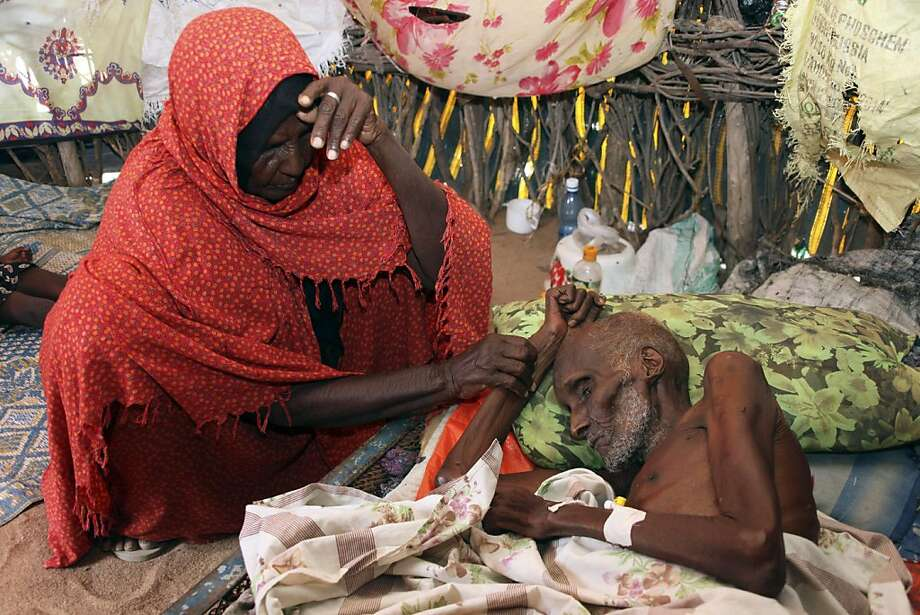 Abdi Ibrahim is helped by his wife Duba Dagane as he lies on his bed suffering from malnourishment,  in Lagbogal, 56 kilometers from Wajir town, Wednesday, July 6, 2011. The worst drought in the Horn of Africa has sparked a severe food crisis and high malnutrition rates, with parts of Kenya and Somalia experiencing pre-famine conditions, the United Nations has said. More than 10 million people are now affected in drought-stricken areas of Djibouti, Ethiopia, Kenya, Somalia and Uganda and the situation isdeteriorating, Photo: Sayyid Azim, AP
