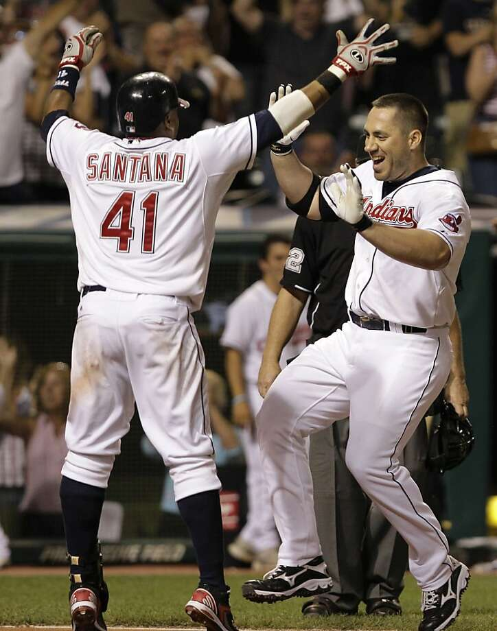 Cleveland Indians' Travis Hafner, right, is greeted at home by teammate Carlos Santana (41) after hitting a walk-off grand slam off Toronto Blue Jays' reliever Luis Perez in the bottom of the ninth inning of a baseball game, Thursday, July 7, 2011, in Cleveland. The Indians won the game 5-4. Photo: Amy Sancetta, AP