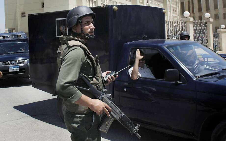 An Egyptian soldier secures the road, as police prisoner vehicles transport three Mubarak-era ministers who were acquitted, out of the Supreme State Security Court after attending their trial session, in Cairo, Egypt Tuesday, July 5, 2011. An Egyptian court has acquitted three Mubarak-era ministers of corruption charges while finding a fourth guilty in absentia. Photo: Nasser Nasser, AP