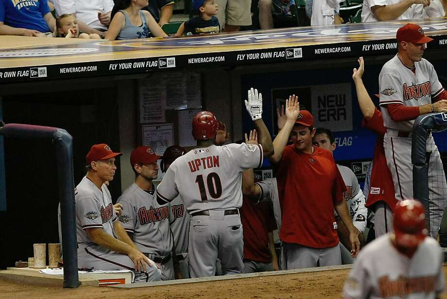 MILWAUKEE, WI - JULY 5: Justin Upton #10 of the Arizona Diamondbacks is congratulated by by team mates after returning to the dugout after hitting a home run against the Milwaukee Brewers at the Miller Park on July 5, 2011 in Milwaukee, Wisconsin. Photo: Scott Boehm, Getty Images