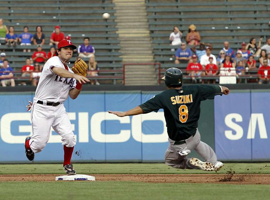 Texas Rangers second baseman Ian Kinsler, left, throws to first after getting Oakland Athletics' Kurt Suzuki out at second in the third inning at Rangers Ballpark in Arlington on Thursday, July 7, 2011, in Arlington, Texas. Photo: Sharon Ellman, MCT