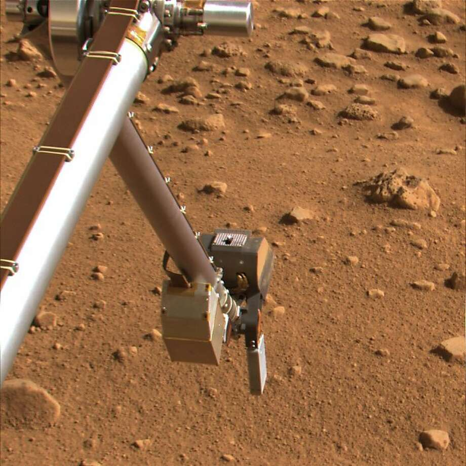 This undated image provided by NASA shows the Phoenix spacecraft's inverted scoop preparing to take soil samples on Mars. NASA's Phoenix spacecraft has detected the presence of a chemically reactive salt in the Martian soil, a finding that if confirmed could make it less friendly to potential life than once believed, according to a report Monday Aug. 4, 2008. (AP Photo/NASA) Photo: Nasa, AP