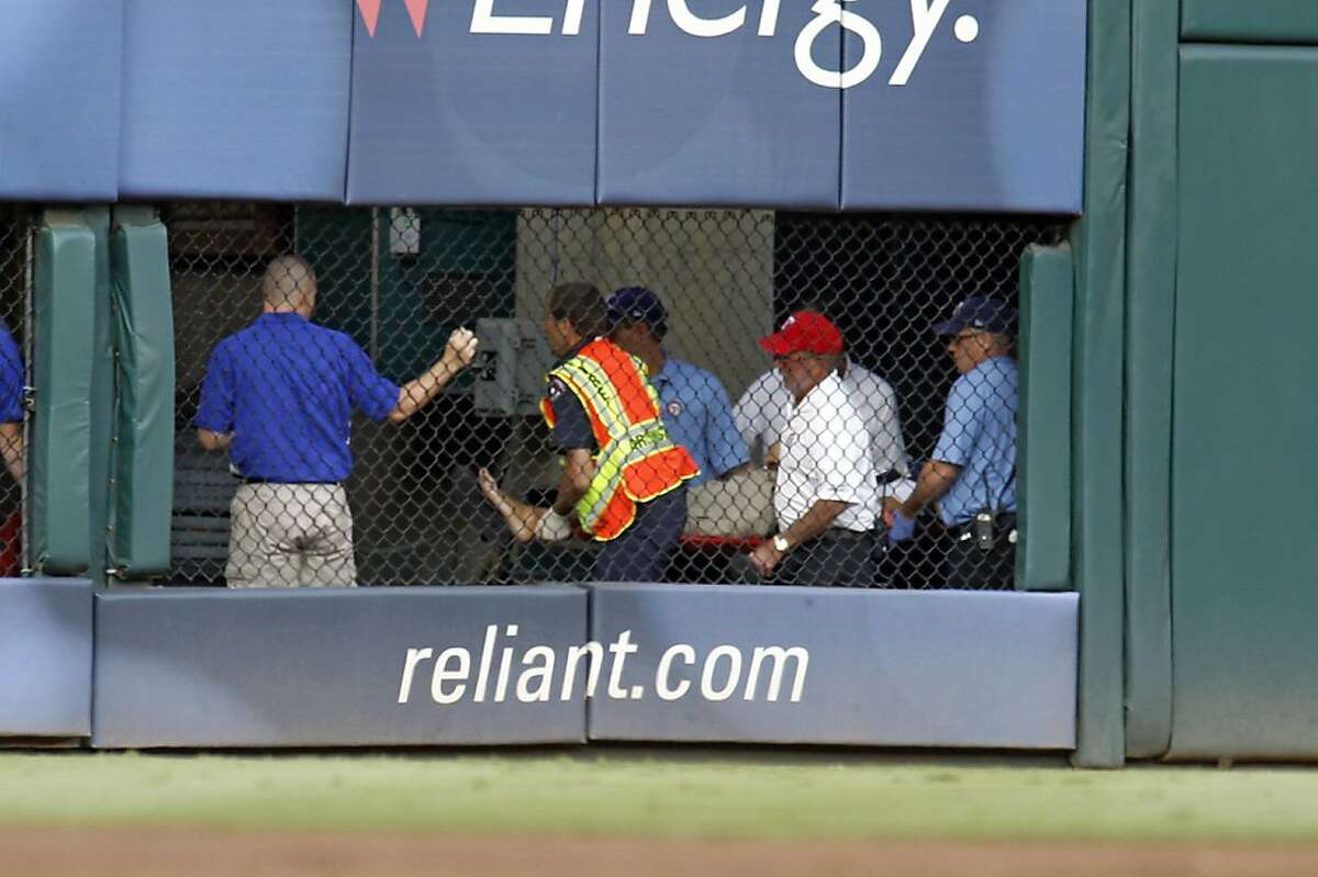 Paramedics move a fan who fell out of the stands between the scoreboard and the outfield seats as the Texas Rangers played host to the Oakland Athletics at Rangers Ballpark in Arlington on Thursday, July 7, 2011, in Arlington, Texas. (Sharon Ellman/Fort Worth Star-Telegram/MCT)