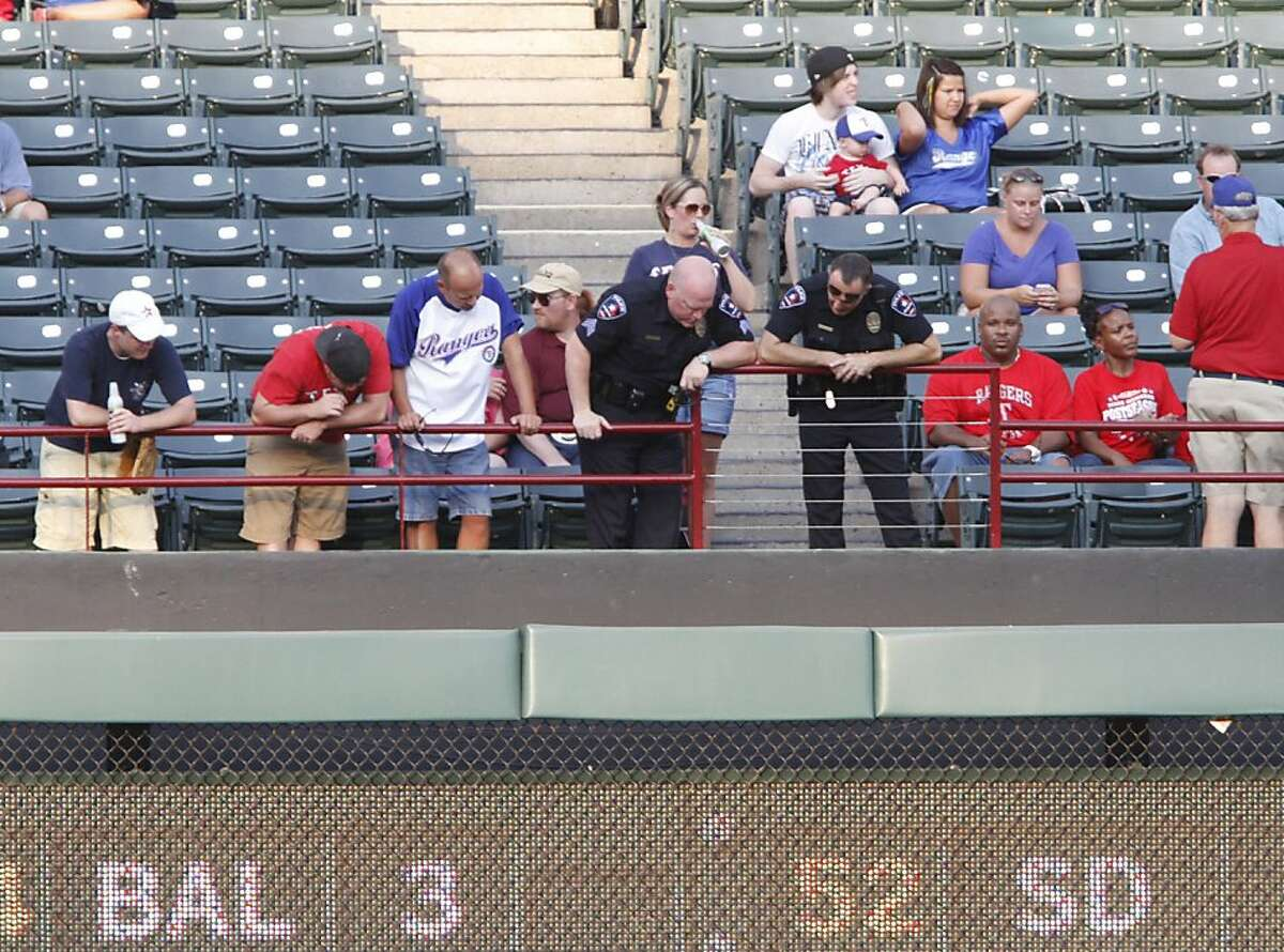 Police and fans look over the railing where a fan fell from the stands during the second inning of a baseball game between the Texas Rangers and the Oakland Athletics, Thursday, July 7, 2011, in Arlington, Texas.