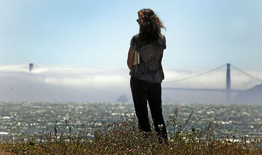 A women watches the fog bank cover the Golden Gate Bridge from the Albany Waterfront Trail Tuesday July 5, 2011. Photo: Lance Iversen, The Chronicle