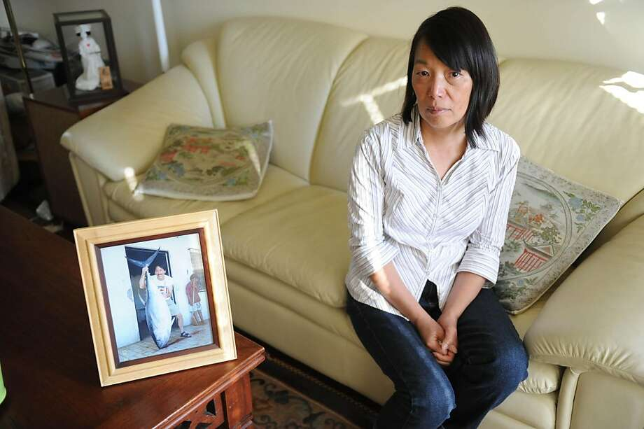Elsie Wong poses for a photo in her home in Berkeley on July 6, 2011. Wong is the wife of Brian Wong (in photo on table) who is one of the men missing at sea after a fishing boat capsized off the Baja coast Sunday. Photo: Susana Bates, Special To The Chronicle