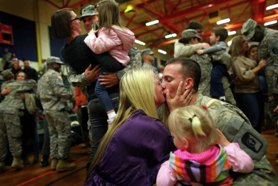 Spc. Scott Cox gets a kiss from his wife Kamara as daugthers Aly, 2, and Emma, 3, greet their dad during a homecoming ceremony for the 62nd Medical Brigade and the 17th Fires Brigade at Joint Base Lewis McChord on Tuesday, December 6, 2011. The return of 170 Army troops from Iraq was the last large homecoming