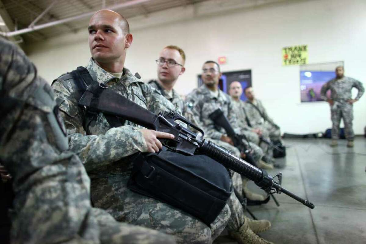 SSgt. Kelly Sawlsville of the 62nd Medical Brigade waits to turn in his weapon at Joint Base Lewis-McChord.