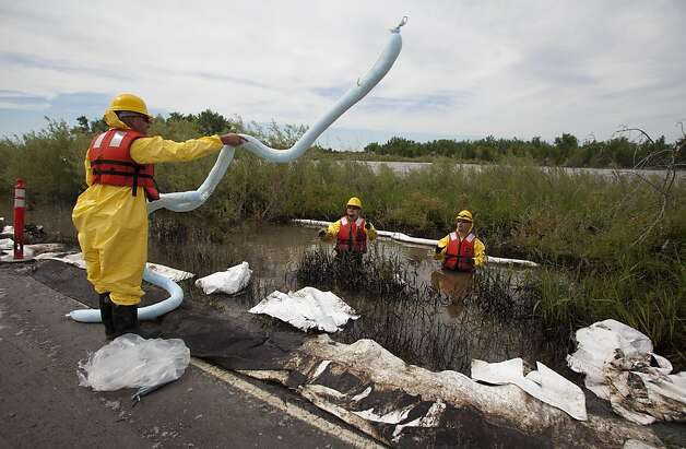 Clean up crews use an absorbent boom to collect oil from along side the Yellowstone River in Laurel, Mont., Monday July 4, 2011. An ExxonMobil pipeline near Laurel ruptured and spilled an estimated 1,000 barrels of crude into the Yellowstone. Photo: Jim Urquhart, AP