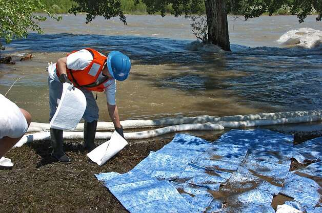 An Exxon Mobil contractors mops up oil along the Yellowstone River near Laurel, Mont. on Monday July 4,2011. An estimated 1,000 barrels of oil spilled from a ruptured pipeline underneath the river. Photo: Matthew Brown, AP