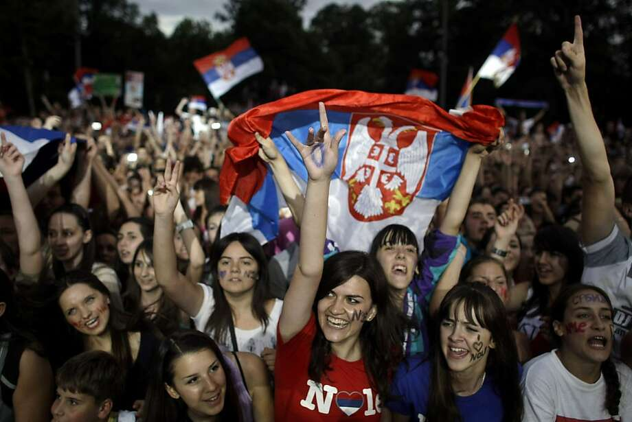 People celebrate and wave Serbian flags at a welcoming ceremony for Novak Djokovic in Belgrade, Serbia, Monday, July 4, 2011. Djokovic received a rapturous welcome in Serbia on Monday following his triumph at Wimbledon and on his first day as the world'stop-ranked tennis player. Photo: Marko Drobnjakovic, AP