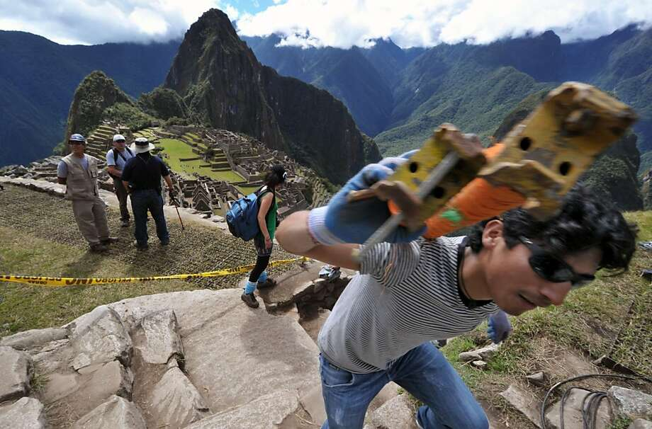 A worker carries stage parts on July 5, 2011 in the Machu Picchu citadel, during preparations for the centennial commemoration of its discovery by American adventurer and archaeologist Hiram Bingham in 1911. The compound, which sits at 2,350 meters abovesea level in the heart of the Urubamba valley in southern Peru, 510 kilometers south of Lima, remained unknown to Spanish conquerors and is now visited by up to 250,000 a year. Photo: Cris Bouroncle, AFP/Getty Images