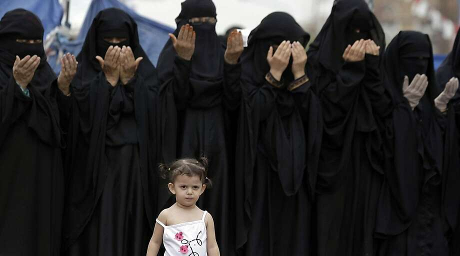 A Yemeni girl, stands in front of female anti-government protestors attending noon prayers, during a demonstration demanding the resignation of Yemeni President Ali Abdullah Saleh, in Sanaa, Yemen, Tuesday, July 5, 2011. Officials in Yemen say airstrikeshave killed six militants and three civilians in southern towns seized by Islamist fighters. Photo: Hani Mohammed, AP