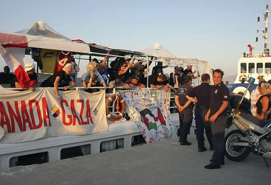 Passengers are seen on the deck of a boat, shortly after the boat was returned to the port by the coast guard in Agiios Nikolaos, northeastern Crete, Greece on Monday, July 4, 2011.  A boat taking part in a flotilla seeking to break Israel's Gaza Strip sea blockade tried to leave the southern island of Crete Monday but was turned back by Greek forces, as the Athens government warned that lives could be lost if the mission goes forward. The coast guard stopped the boat shortly after it set sail without permission from the port of Agios Nikolaos in northeastern Crete, and towed it back into port Photo: AP