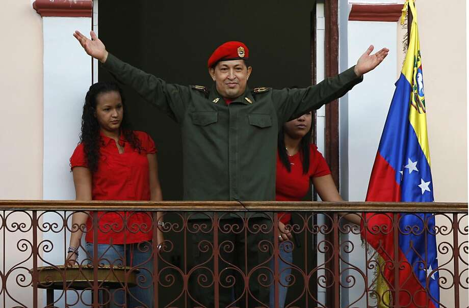 Venezuela's President Hugo Chavez greets supporters next to his two daughters: Rosa Virginia, left, and Maria Gabriela at a balcony of the Miraflores presidential palace in Caracas, Venezuela, Monday, July 4, 2011. Chavez returned to Venezuela from Cuba on Monday morning, stepping off a plane hours before dawn and saying he is feeling better as he recovers from surgery that removed a cancerous tumor. Photo: Ariana Cubillos, AP