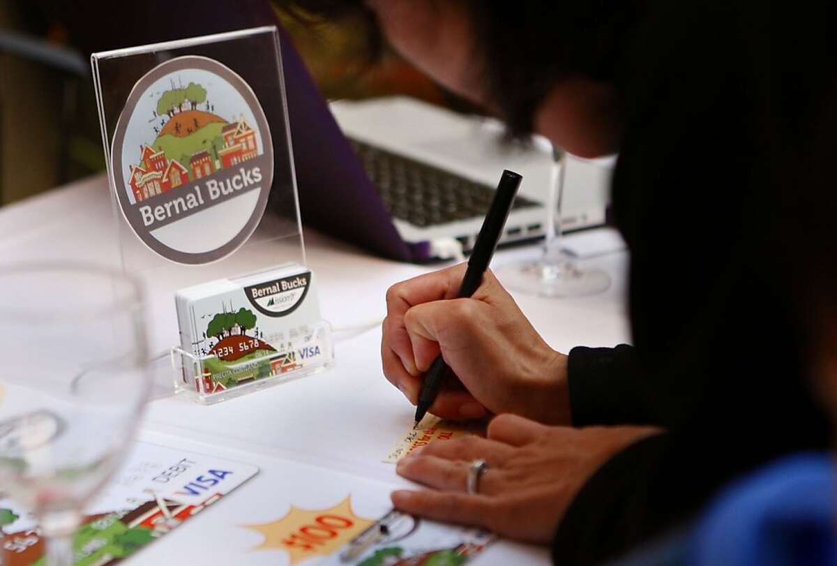 Bernal Heights resident Christina Bryant signs her name on a card for a prize drawing at the Bernal Bucks launch party in San Francisco Calif., on June 21, 2011.