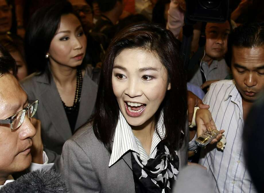 Yingluck Shinawatra, the leader of Pheu Thai Party, center, talks with reporters upon her arrival at a hotel for a meeting with leaders of the coalition partners Monday, July 4, 2011 in Bangkok, Thailand. Yingluck, sister of ousted Prime Minister ThaksinShinawatra, announced an agreement Monday to form a five-party coalition government after her party won a landslide victory in Thailand's parliamentary elections. Photo: Apichart Weerawong, AP