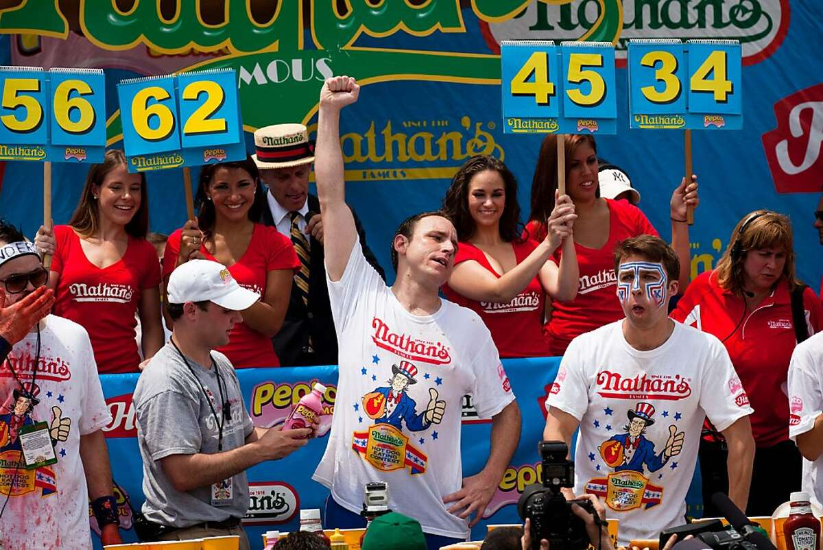 Four-time reigning champion Joey Chestnut, center, raises his arm in victory as he wins his fifth Nathan's Famous Hot Dog Eating World Championship with a total of 62 hot dogs and buns, Monday, July 4, 2011, at Coney Island, in the Brooklyn borough of NewYork.