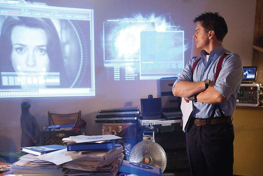"Captain Jack Harkness (John Barrowman) and a computer image of Torchwood colleague Gwen Cooper (Eve Myles) in the fourth season of ""Torchwood."" Photo: Courtesy Starz/BBC"