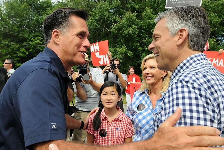AMHERST, NH - JULY 4: Republican presidential candidates Former Ambassador to China Jon Huntsman (R) and former Massachusetts governor Mitt Romney (L) greet to each other prior to marching in a Fourth of July parade as Huntsman's wife Mary Kaye (2nd R) and daughter Gracie Mei look on July 4, 2011 in Amherst, New Hampshire. Romney, considered the republican front runner,  raised nearly 20 million in the second quarter. (Photo by Darren McCollester/Getty Images)  *** BESTPIX *** Photo: Darren McCollester, Getty Images