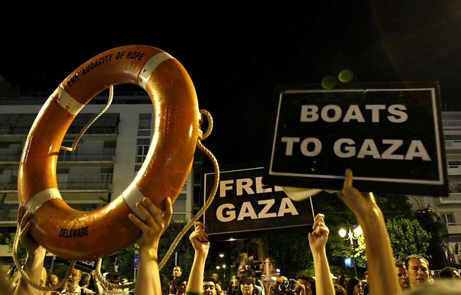 Activists of Gaza flotilla hold banners  during a gathering outside the US embassy in Athens, Greece, Sunday, July 3, 2011. Organizers of a Gaza-bound flotilla said Sunday they have not abandoned their plans to breach Israel's sea blockade of the territory despite a Greek government ban on their vessels leaving the country's ports. Photo: Petros Karadjias, AP