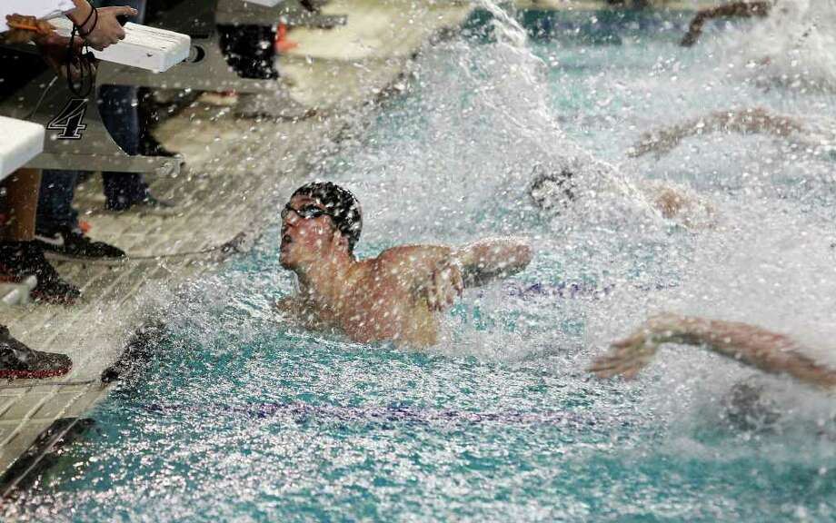 Jimmy Feigen looks to the clock while other swimmers finish their last strokes on Tuesday, Dec. 6, 2011 at the Davis Natatorium. Photo: TOM REEL, SAN ANTONIO EXPRESS-NEWS  / © 2011 San Antonio Express-News