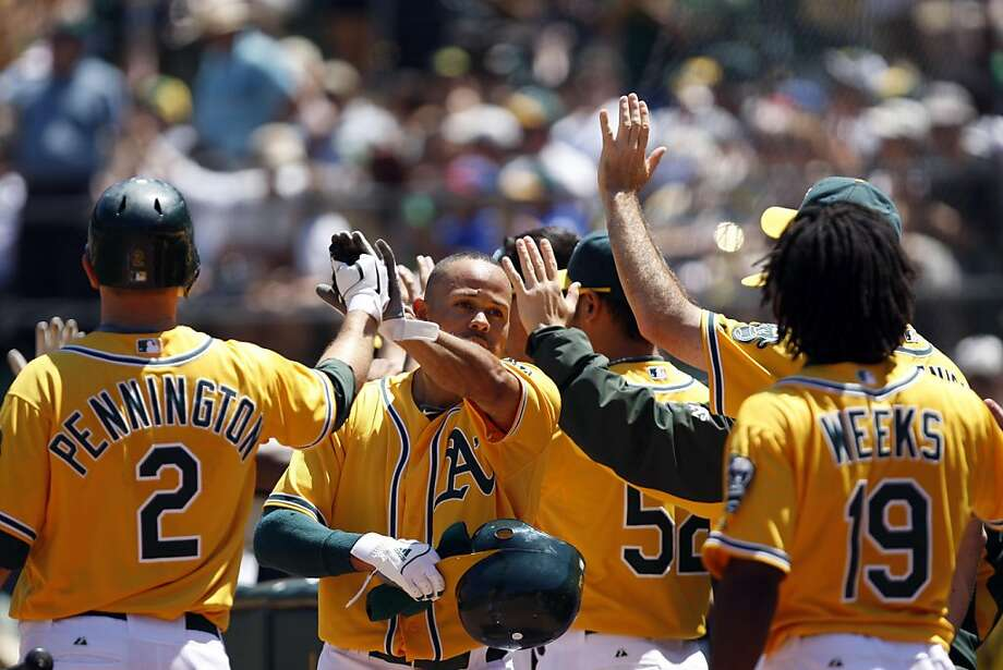 Coco Crisp returns to the dugout after scoring on a two run double by David DeJesus in the fourth inning. The Oakland A's beat the Arizona Diamondbacks 7-2 at the O.co Coliseum in Oakland, Calif., on Sunday, July 3, 2011. The A's won the series against the Diamondbacks 2-1. Photo: Maddie McGarvey, The Chronicle