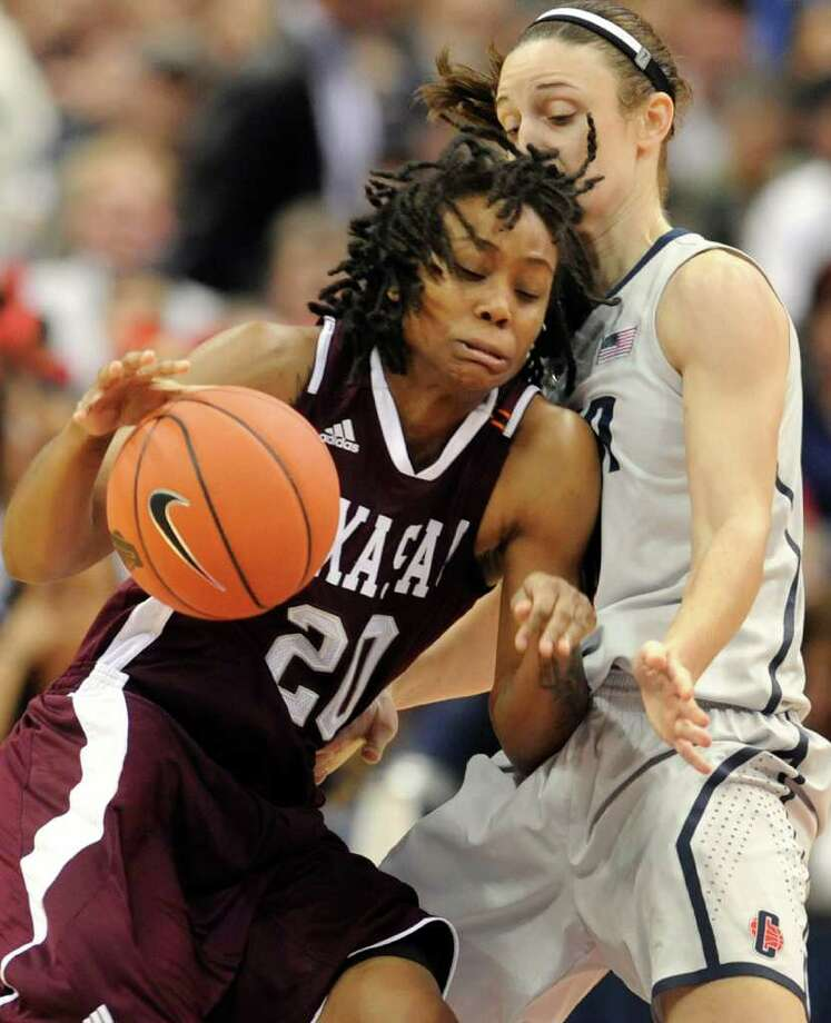 Texas A&M's Tyra White, left, is guarded by Connecticut's Kelly Faris, right in the first half of an NCAA college basketball game in Hartford, Conn., Tuesday, Dec. 6, 2011. Photo: Jessica Hill, Associated Press