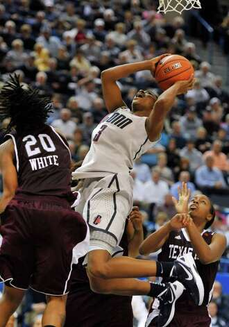 Connecticut's Tiffany Hayes, center, drives to the basket while guarded by Texas A&M's Tyra White in the second half of an NCAA college basketball game in Hartford, Conn., Tuesday, Dec. 6, 2011.  Connecticut won 81-51. Photo: Jessica Hill, Associated Press
