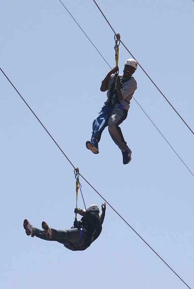Thrill seekers enjoy the ride down a 750-foot long zipline stretching high above Justin Herman Plaza. The high adrenaline ride is available 7 days a week throughout the summer. Photo: Paul Chinn, The Chronicle