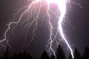 In a June 28, 2011 photo, a blast of lightning bolts shoot down towards Bend Ore. during a storm . The U.S. Forest Service said it recorded 483 lightning strikes in central Oregon during the storm, which caused a small fire near Cultus Lake.