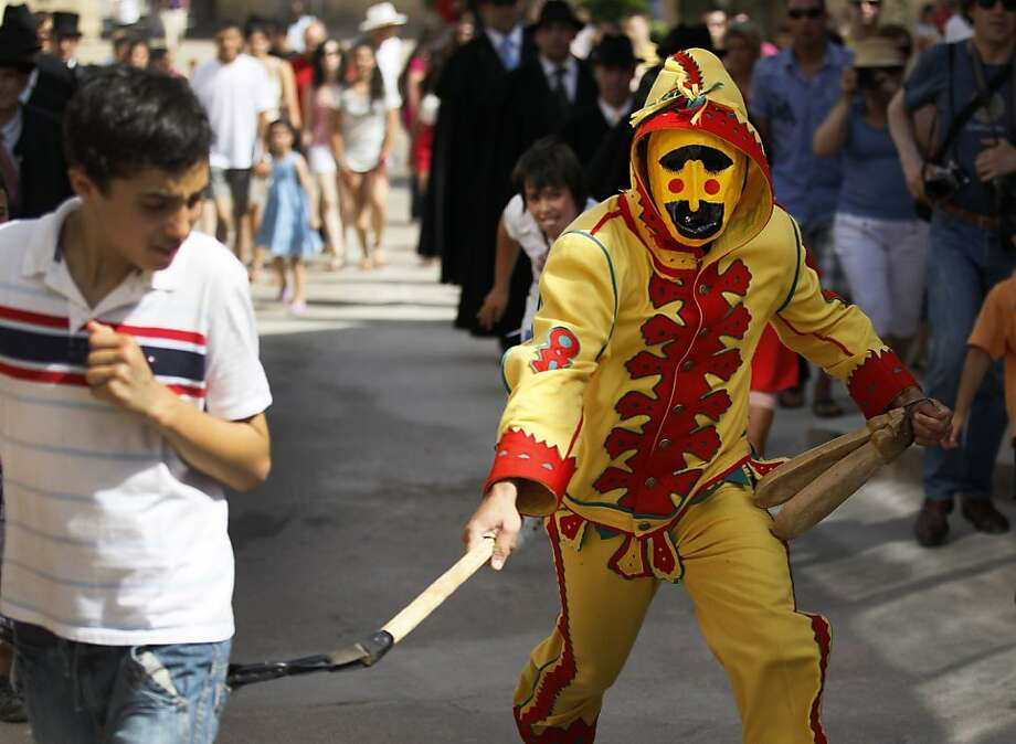 A man dressed up as the devil walks in the street as he chases the children during 'El Colacho', the 'baby jumping festival'  on June 26, 2011  in the village of Castrillo de Murcia, near Burgos. Baby jumping (El Colacho) is a traditional Spanish practicedating back to 1620 that takes place annually to celebrate the Catholic feast of Corpus Christi.  During the act - known as El Salto del Colacho (the devil's jump) or simply El Colacho – men dressed as the Devil (known as the Colacho) jump over babiesborn the last twelve months of the year who lie on mattresses in the street. Photo: Cesar Manso, AFP/Getty Images