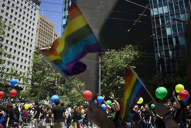 Observers of the annual San Francisco Pride parade wave rainbow flags as the ...