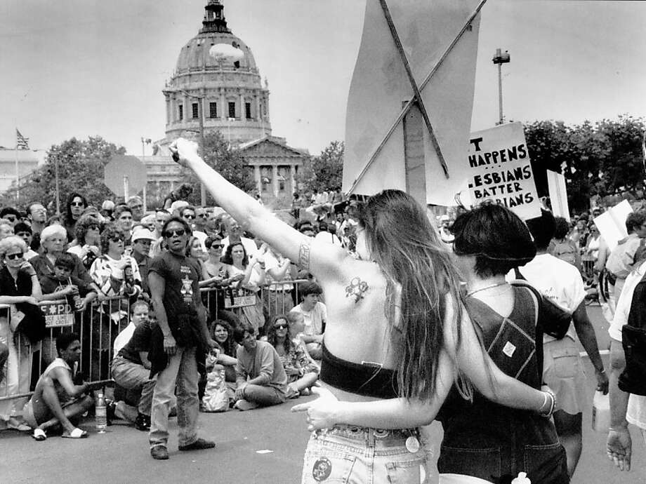 Two women near the end of the 1992 Gay Pride Parade, with San Francisco City Hall in the background. Photo: Scott Sommerdorf, The Chronicle