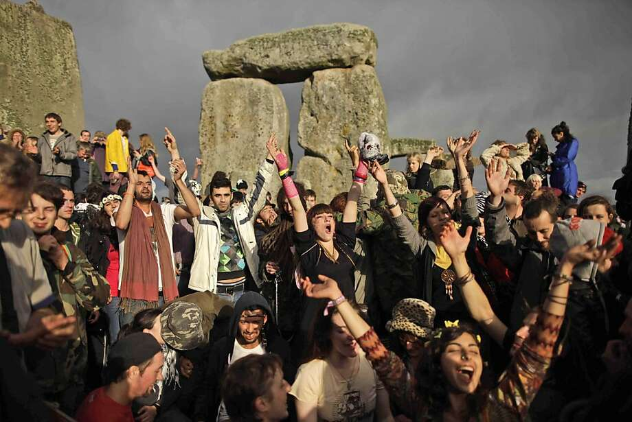 Revellers cheer as the sun finally breaks through the clouds more than a couple of hours after sunrise during the summer solstice at Stonehenge, near Salisbury in England, Tuesday, June 21, 2011.  The ancient stone circle of Stonehenge is a World HeritageSite erected between approximately 3000BC and 1600BC and despite years of research the reason behind its construction remains a mystery. The summer solstice in the northern hemisphere occurs annually on June 21 and is the time at which the sun is at itsnorthernmost point in the sky. Photo: Matt Dunham, AP