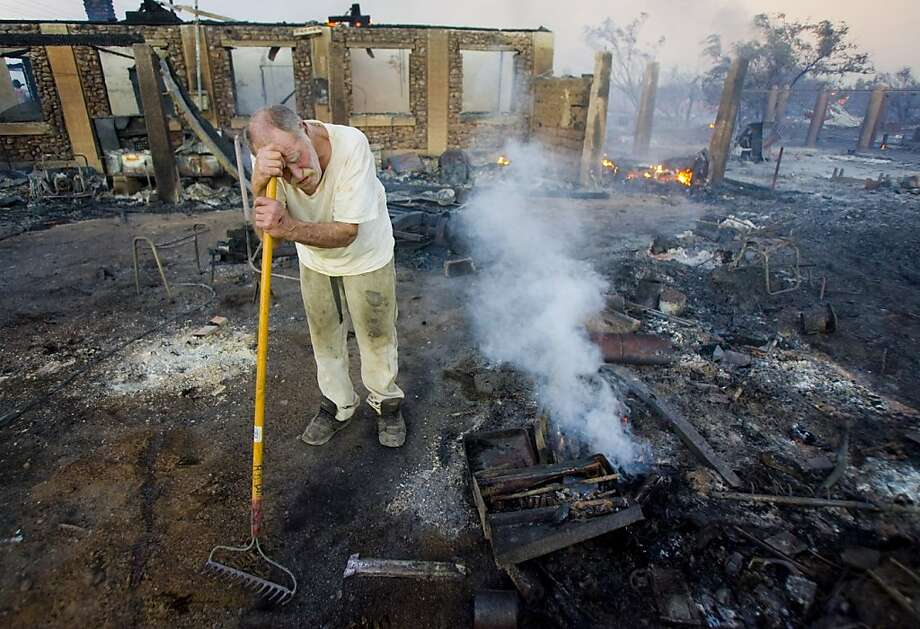 Pete Tunstall leans on his rake while at his home that burned along the south side of Ramsey Road near State Route 92 as the Monument Fire burns on Sunday, June 19, 2011 near Sierra Vista, Ariz. Tunstall lived in this house since 1969. Photo: Dean Knuth, Arizona Daily Star