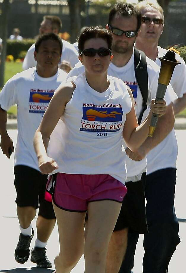 SFPD officer Jenna Fiorello from the Southern station carrying the Special Olympics torch while passing Pier 39 in San Francisco, Calif., on Tuesday afternoon,  June 20, 2011. Photo: Liz Hafalia, The Chronicle