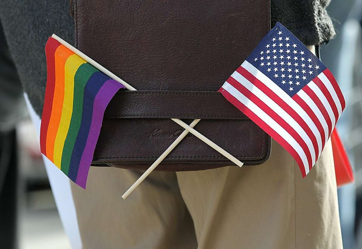SAN FRANCISCO, CA - JUNE 13: A gay pride and an American flag hang from a shoulder bag during a demonstration outside of the Phillip Burton Federal Building on June 13, 2011 in San Francisco, California. Sponsors of Proposition 8, a California ballot measure that would deny same-sex couples to marry in the state, are back in court today to ask a federal judge to nullify U.S. District Judge Vaughn Walker's decision to overturn California's ban on same-sex marriage.