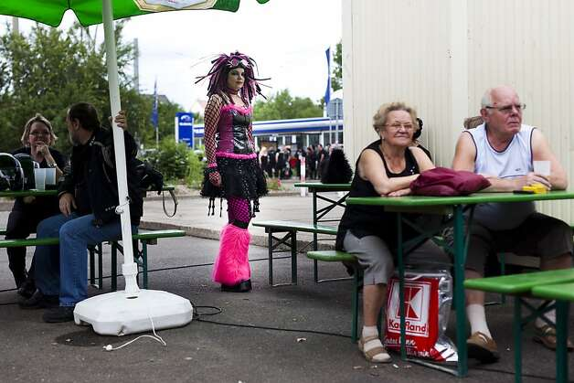 A gothic rock music enthusiast stays behind spectators during the annual Wave Gotik music festival on June 11, 2011 in Leipzig, Germany. The festival began in the 1990s and has since grown into one of the biggest gatherings ofGoth scene followers in Europe with around 20,000 participants. Many of those attending wear elaborate outfits and make-up for which they require hours of painstaking preparation and that also show a departure from the traditional black of the Goth scene. Punk remains a strong influence in todays Goth style as witnessed in Leipzig, but newer trends, with names like Cybergoth and Steampunk, have emerged that blend bold colors, Victorian fashion elegance and 19th and 20th century factory accessories into Photo: Carsten Koall, Getty Images