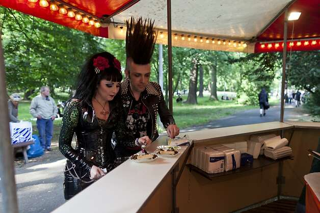 Gothic rock music enthusiasts eat a curry sausage at a snack stand during the annual Wave Gotik music festival on June 11, 2011 in Leipzig, Germany. The festival began in the 1990s and has since grown into one of the biggest gatherings of Goth scene followers in Europe with around 20,000 participants. Many of those attending wear elaborate outfits and make-up for which they require hours of painstaking preparation and that also show a departure from the traditional black of the Goth scene. Punk remains a strong influence in todays Goth style as witnessed in Leipzig, but newer trends, with names like Cybergoth and Steampunk, have emerged that blend bold colors, Victorian fashion elegance and 19th and 20th century factory acce Photo: Carsten Koall, Getty Images