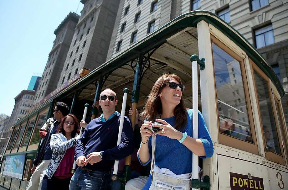 File photo of passengers riding a cable car traveling along Powell Street on June 9, 2011 in San Francisco. A  60-year-old man was taken to a hospital Saturday afternoon after falling from a cable car. Photo: Justin Sullivan, Getty Images