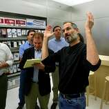 Steve Jobs points out the ceiling to amazed reporters at the new Apple mini store in Stanford shopping center in Palo Alto, CA on October 14, 2004.