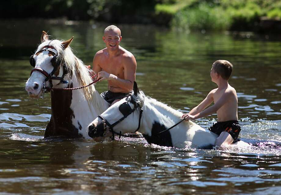 Travelers wash their horses in the River Eden in preparation for selling at the Appleby Horse Fair in Appleby, England. Photo: Christopher Furlong, Getty Images