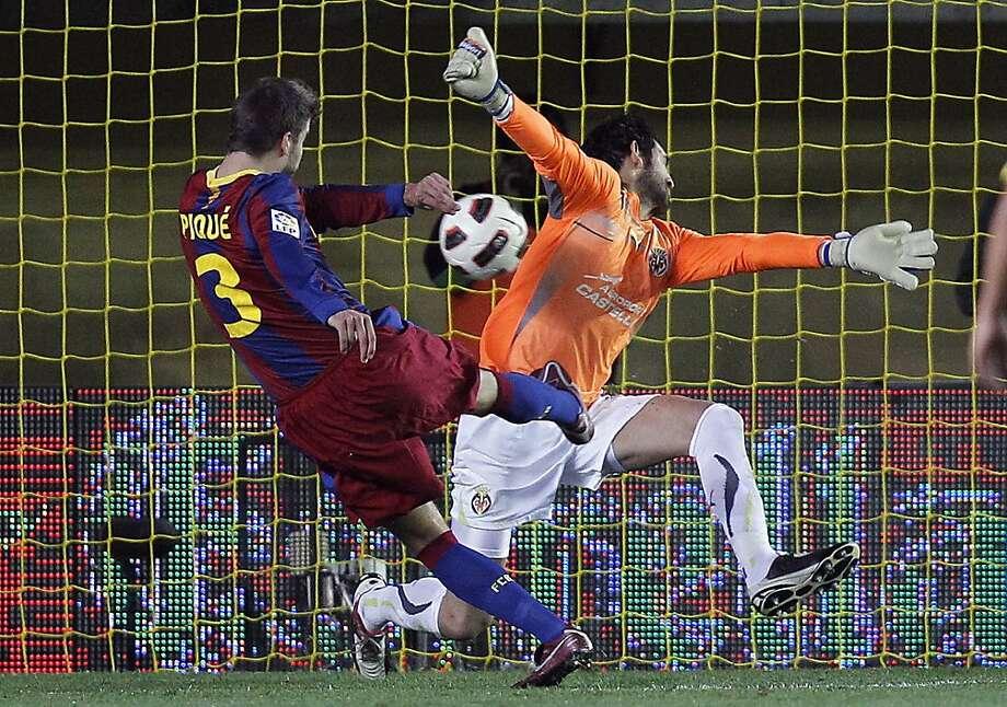 Barcelona's Gerard Pique, left, shoots to score pass Villarreal's goalkeeper Diego Lopez, right, during their Spanish La Liga soccer match at Madrigal stadium in Villarreal, Saturday, April  2, 2011. Photo: Alberto Saiz, AP