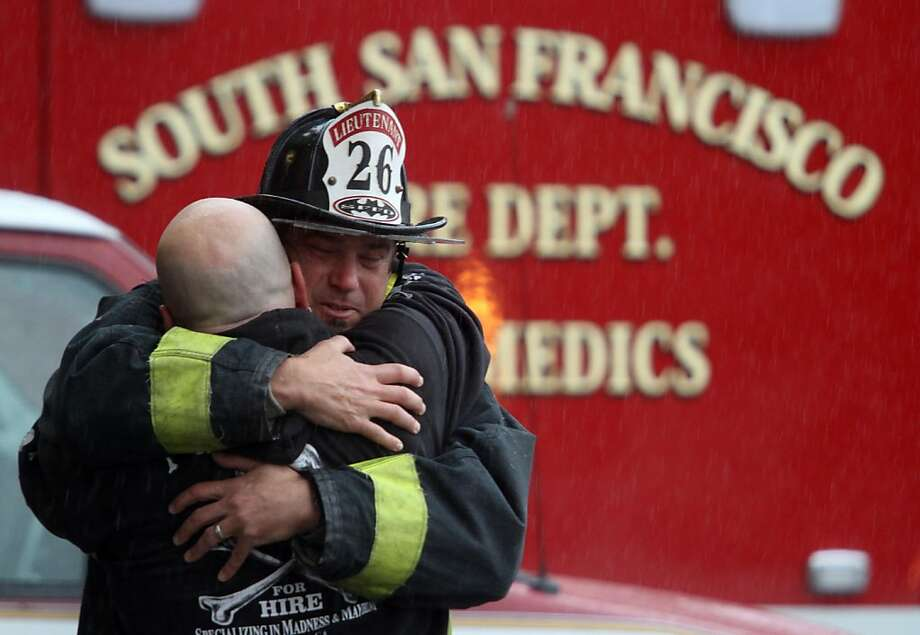 Lt. Mark Hardemon, facing, hugs another mourner as the body of San Francisco firefighter Anthony Valerio is removed from San Francisco General Hospital on Saturday, June 4, 2011. Valerio died from injuries sustained while fighting a two-alarm house fire in the Diamond Heights neighborhood on Thursday. Photo: Mathew Sumner, Special To The Chronicle