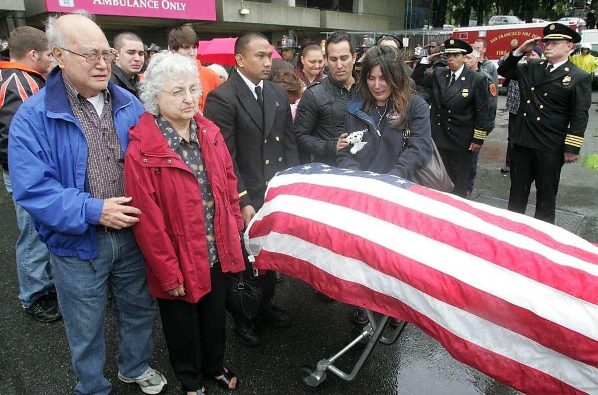Frank and Lorraine Valerio, left, the parents of San Francisco firefighter Anthony Valerio, along with other family members , stand by as Valerio's body is taken by a medical examiner from San Francisco General Hospital on Saturday. Valerio died from injuries sustained while fighting a two-alarm house fire in the Diamond Heights neighborhood on Thursday.