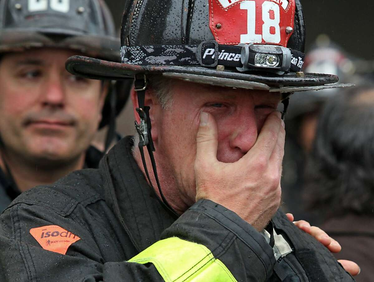 Firefighter Richard Faust, a co-worker of Anthony Valerio, cries as the casket with Valerio's body is taken by a medical examiner from San Francisco General Hospital on Saturday. Valerio died from injuries sustained while fighting a two-alarm house fire in the Diamond Heights neighborhood on Thursday.