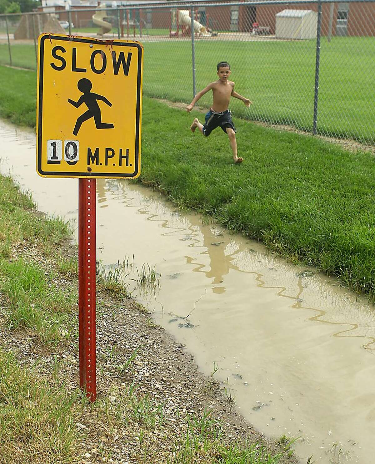Jace Milbourne, 7, runs past a water filled ditched Thursday, June 2, 2011, near the Riverside Unified Elementary School District in Elwood, Kan. The small Kansas town on the bank of the Missouri River is threatened by the rising waters.
